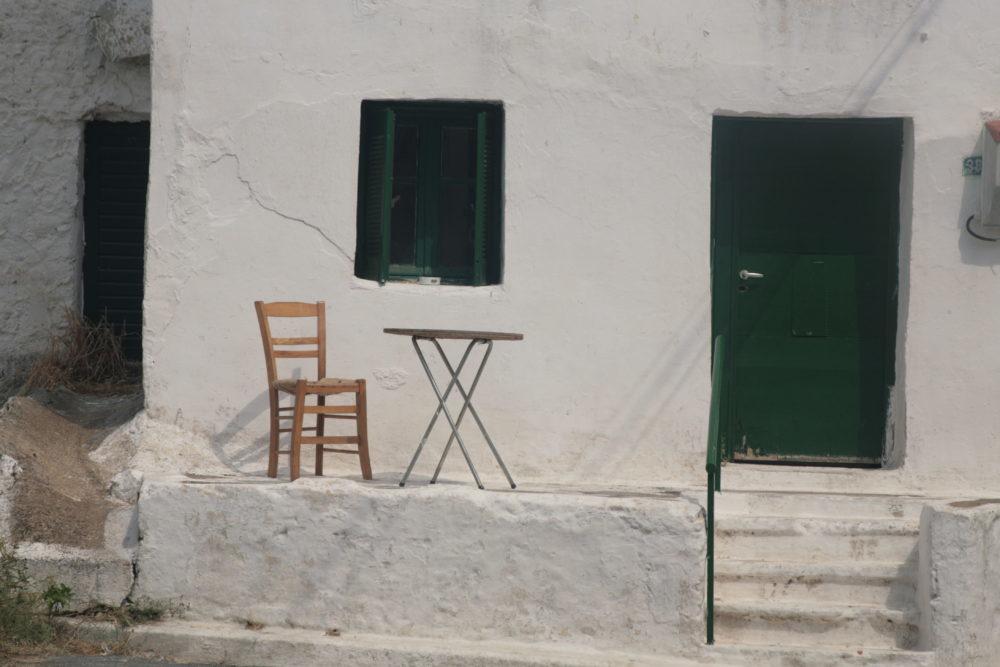 Sedia e tavolo fuori da una casa. Nell'invidia nessuno vince.